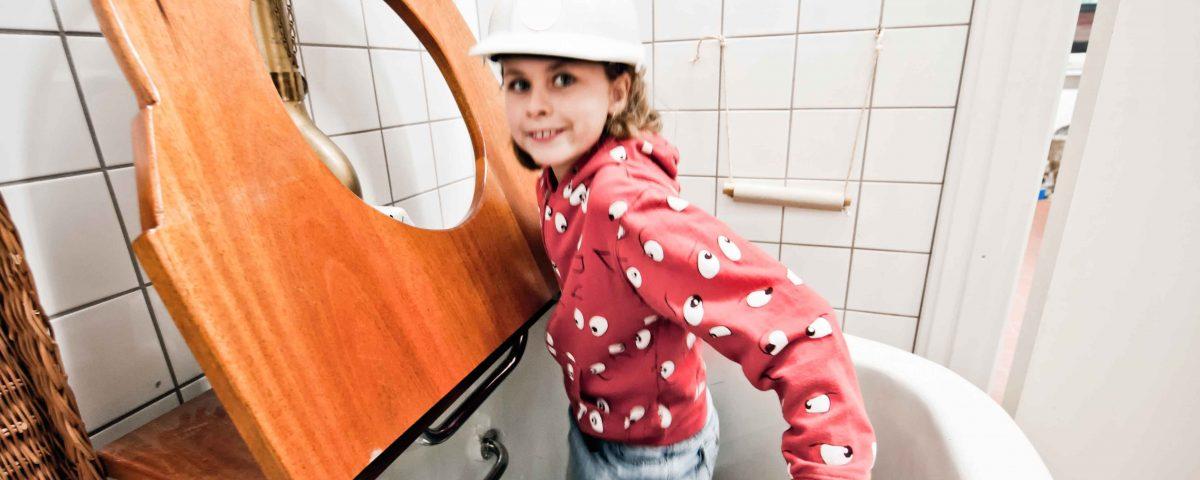 Pige med sikkerhedshjelm kravler ned i kæmpetoilet